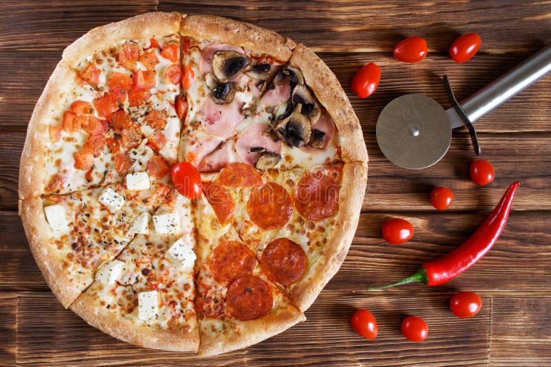 自创四片断比萨用意大利辣味香肠,蒜味咸腊肠,红辣椒,火腿,蘑菇,乳酪,在一自然木的蕃茄谎言 免版税库存照片