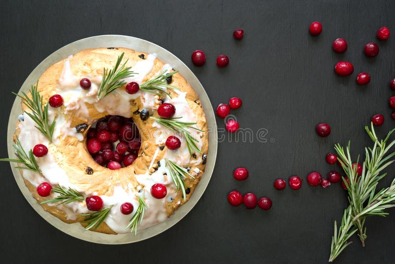 自创圣诞节蛋糕用装饰品蔓越桔和迷迭香在装饰板材 顶视图 库存图片