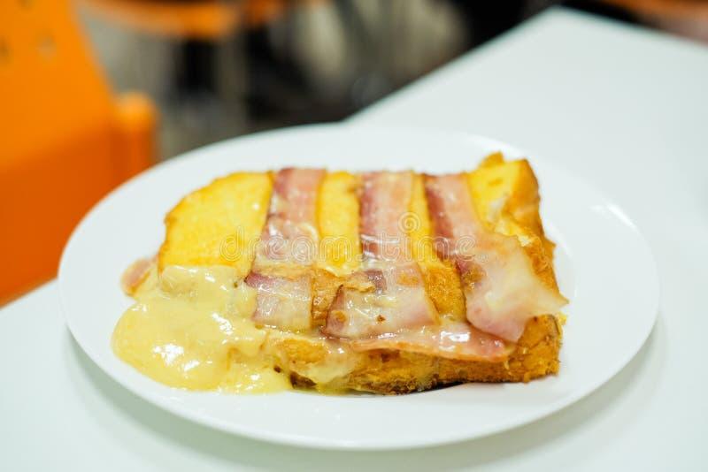 自创在与切达乳酪&无盐干酪乳酪`服务的面包上把放的`烟肉和火腿在食物背景或纹理的-断裂白色板材 库存照片