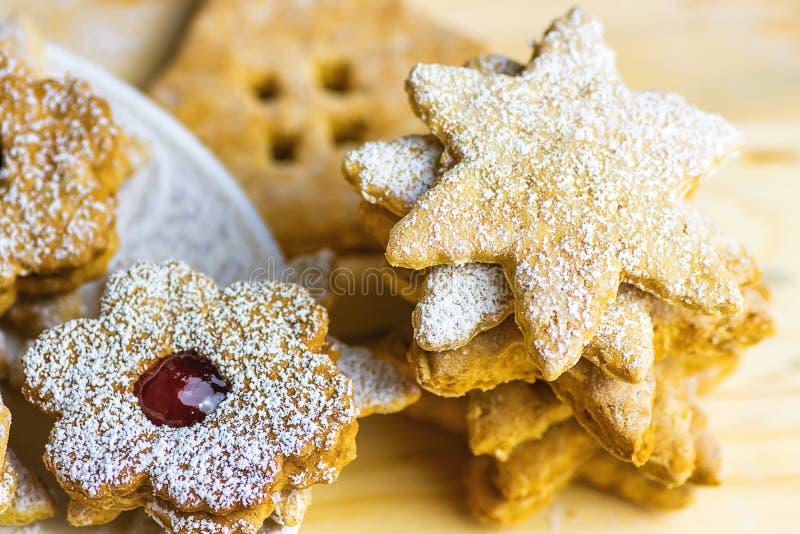 自创姜饼和一种油脂含量较高的酥饼各种各样的形状星议院花用果酱Linzer搽粉了 板材木头表 免版税库存照片