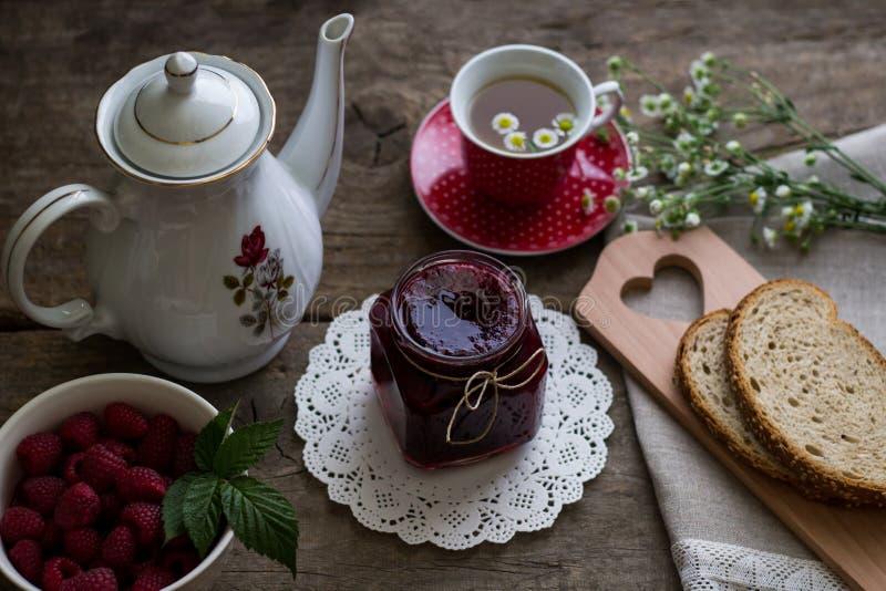 自创山莓果酱、新鲜的莓、面包和春黄菊 免版税库存照片