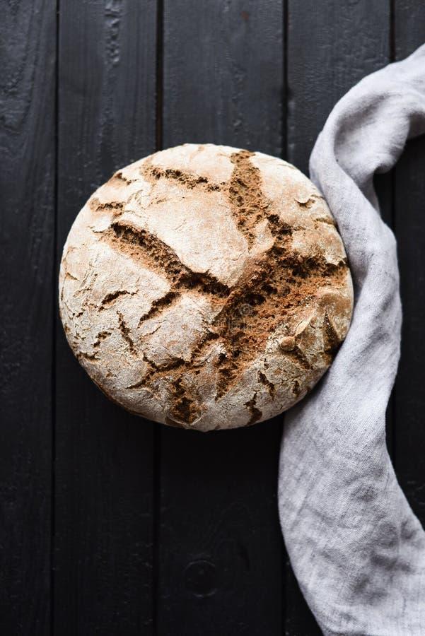 自创工匠面包 酸面团新近地被烘烤的圆的大面包与亚麻布的在黑背景顶视图 图库摄影