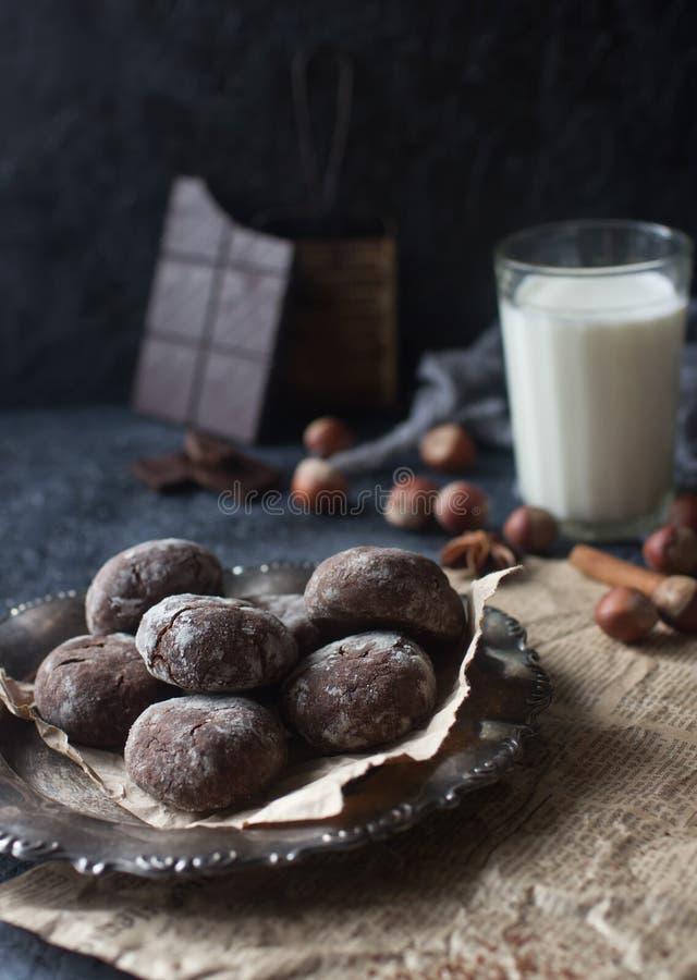 自创巧克力在搽粉的糖、巧克力曲奇饼与镇压和一杯卷曲牛奶 图库摄影