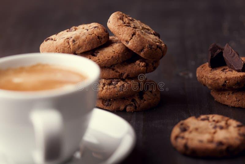 自创巧克力曲奇饼和一杯咖啡在黑暗的老木桌上的 免版税图库摄影