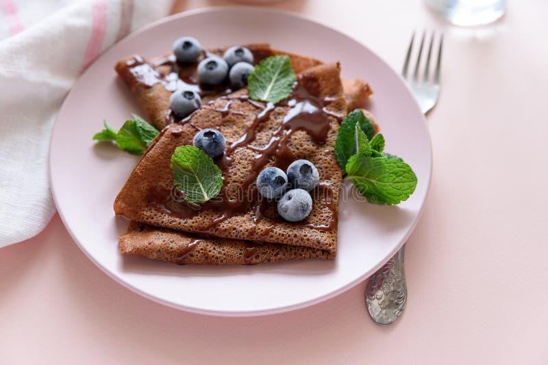 自创巧克力绉纱服务用蓝莓、调味汁和薄荷叶在桃红色背景 选择聚焦 顶视图 复制空间 图库摄影