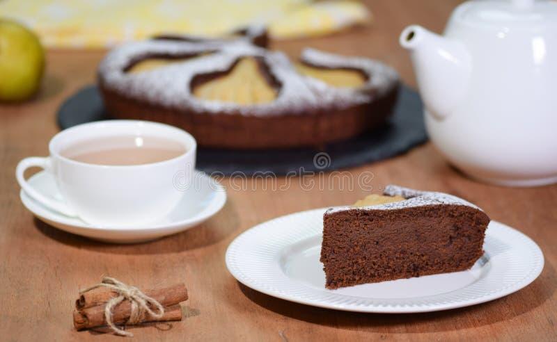 自创巧克力蛋糕片断用在土气背景的梨 图库摄影
