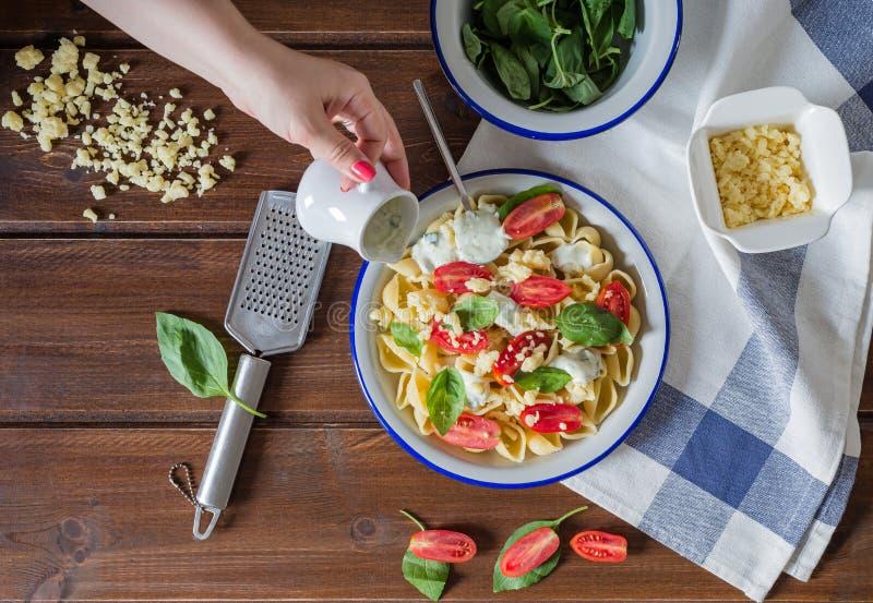 自创意大利面团、酸性稀奶油与pesto,cherri蕃茄和蓬蒿 免版税图库摄影