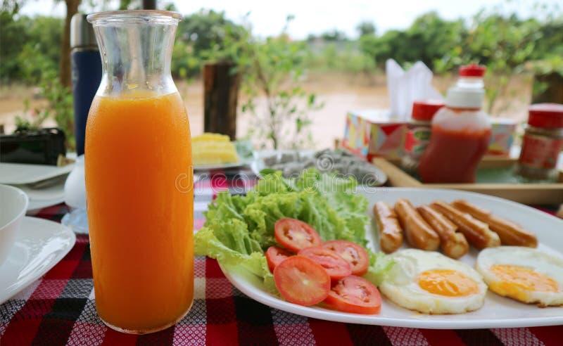 自创新鲜的被紧压的蜜桔橙汁过去玻璃水瓶服务与早餐一块大板材  库存图片