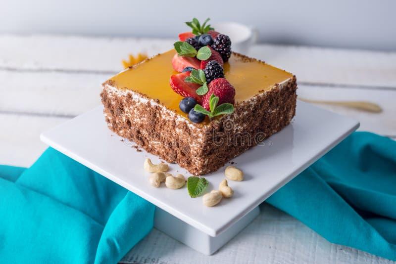 自创方形的蛋糕装饰在黄色果冻和莓果顶部用薄菏在轻的背景 库存照片