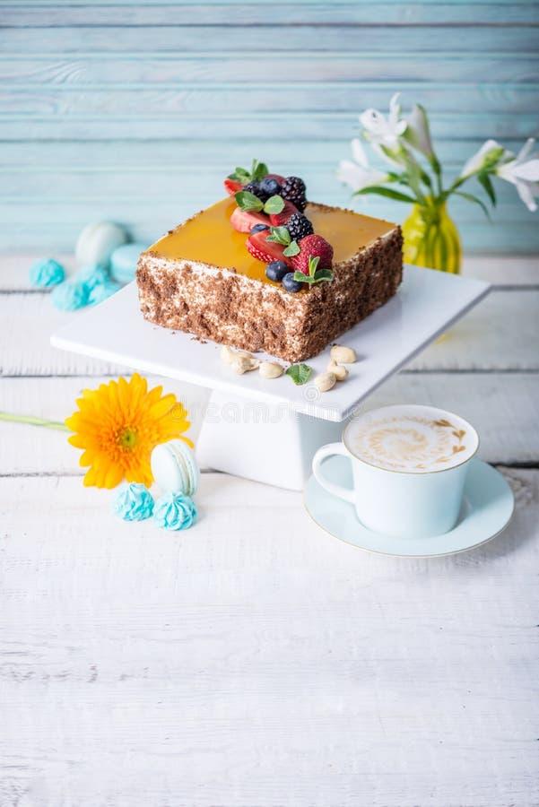 自创方形的蛋糕装饰在黄色果冻和莓果顶部用薄菏在轻的背景 免版税库存图片