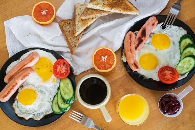 自创早餐用煎蛋多士香肠果菜类咖啡和在顶视图舱内甲板的橙汁放置概念 免版税库存图片