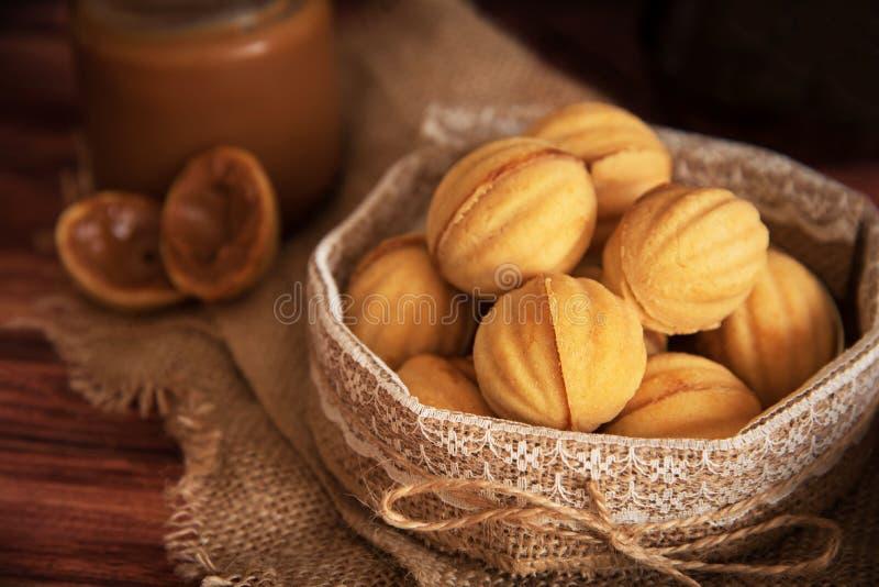 自创曲奇饼塑造了有奶油煮沸的浓缩的milkt的坚果在木桌上 免版税库存照片