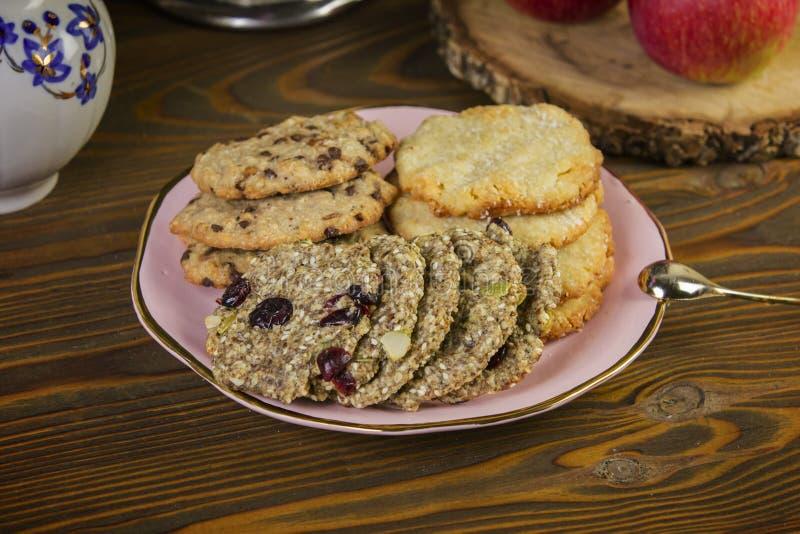自创曲奇饼:椰子,燕麦粥,巧克力,在一张木桌上,与茶罐,在土气构成的背景与 免版税库存照片