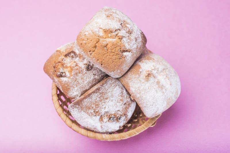 自创杯形蛋糕洒与在一个柳条筐的搽粉的糖在桃红色丁香背景 图库摄影