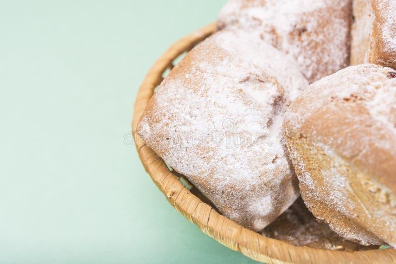 自创松饼用葡萄干和在一个柳条筐的糖粉末反对一种轻的薄荷的颜色 免版税库存图片