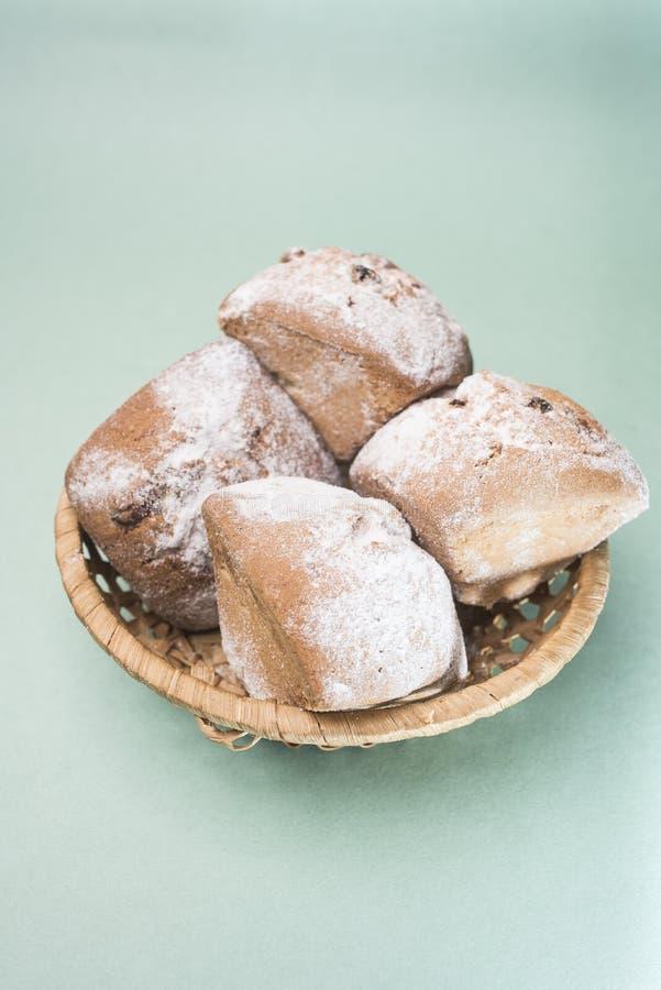 自创松饼用葡萄干和搽粉的糖在一个柳条筐反对一种轻的薄荷的颜色,垂直的框架 库存图片