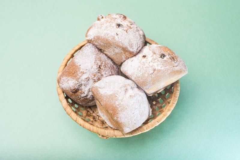 自创松饼用葡萄干和搽粉的糖在一个柳条筐反对一种轻的薄荷的颜色 免版税库存图片