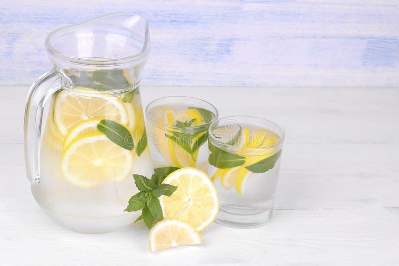 自创柠檬水用柠檬和薄菏在一个玻璃水罐和一块玻璃在柠檬旁边在白色和蓝色木背景 免版税图库摄影