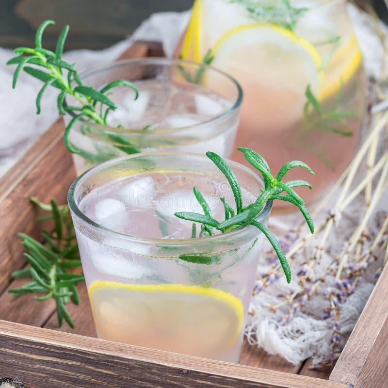 自创柠檬水用淡紫色、新鲜的柠檬和迷迭香在一个木盘子,方形的格式 库存照片