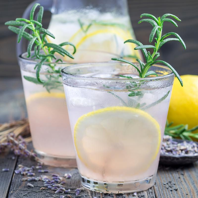 自创柠檬水用淡紫色、新鲜的柠檬和迷迭香在木背景,方形的格式 免版税库存照片