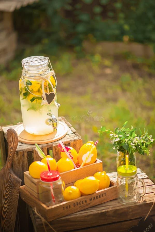自创柠檬水销售概念 柠檬,薄菏,在箱子的鸡尾酒罐头柠檬水特写镜头的 在分配器和警察的自创柠檬水 免版税图库摄影