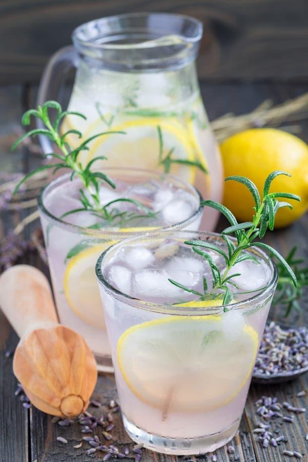 自创柠檬水用淡紫色、新鲜的柠檬和迷迭香在木桌上,垂直 免版税库存图片