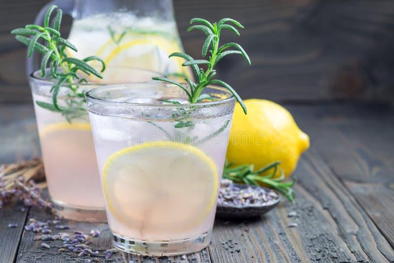 自创柠檬水用淡紫色、新鲜的柠檬和迷迭香在木桌上,水平,复制空间 库存图片
