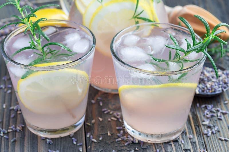 自创柠檬水用淡紫色、新鲜的柠檬和迷迭香在木桌上,水平 免版税图库摄影