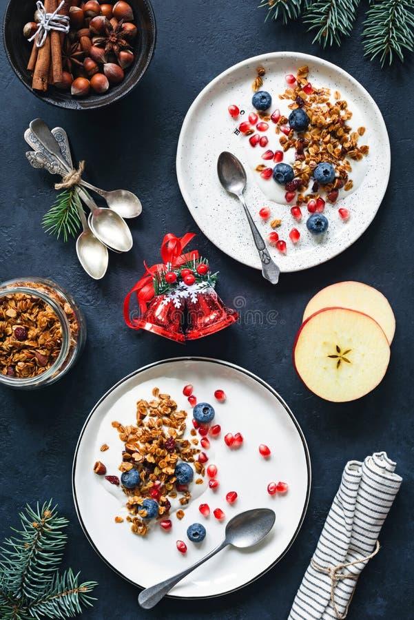 自创格兰诺拉麦片、蓝莓石榴种子和酸奶 健康圣诞节早餐顶视图 库存图片