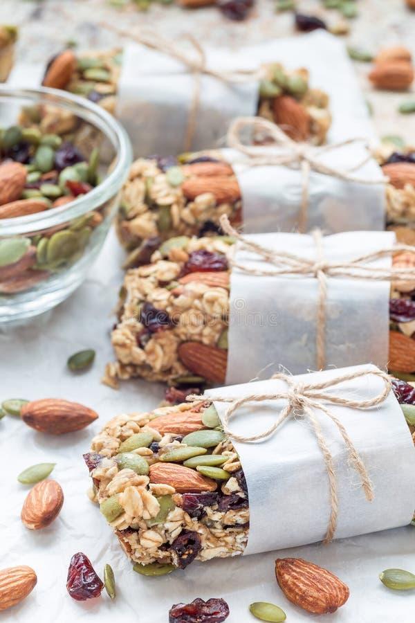 自创格兰诺拉麦片强身糕用无花果,燕麦粥、杏仁、干蔓越桔和南瓜籽,垂直 免版税库存照片