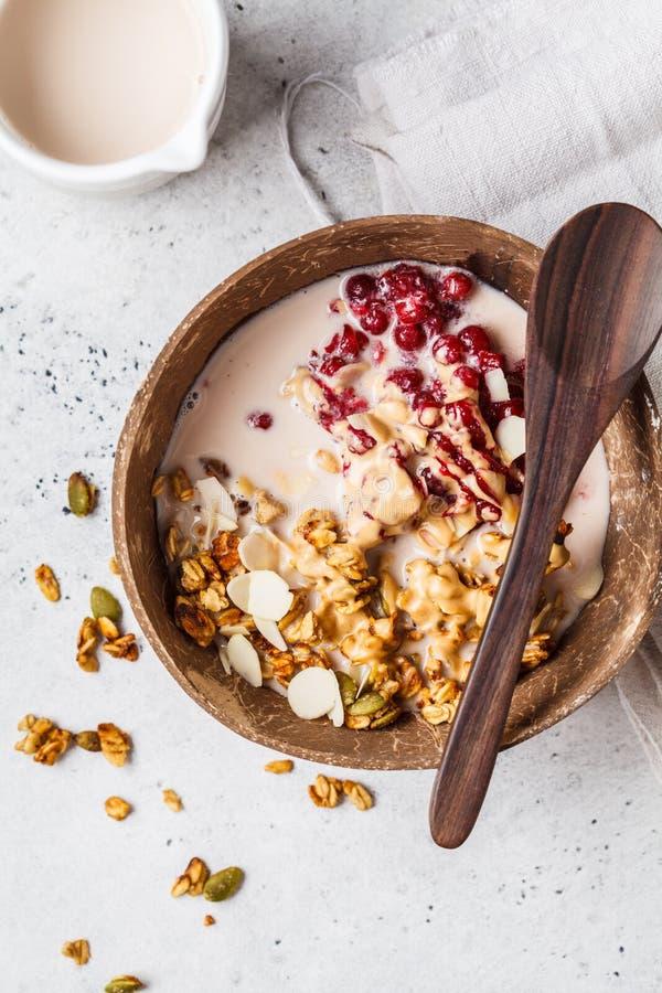 自创格兰诺拉麦片用蔓越桔和花生酱在椰子碗,垂直 免版税库存照片