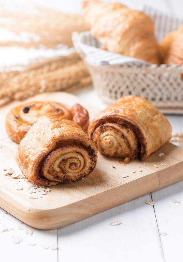 自创桂皮卷面包和面包店白色木头的 图库摄影