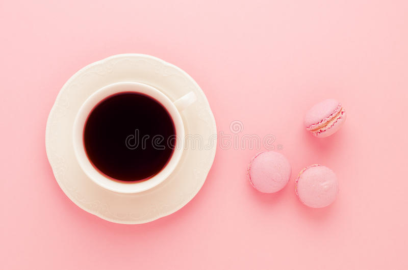 自创桃红色的蛋白杏仁饼干和一杯咖啡在桃红色背景的定了调子,顶视图 图库摄影