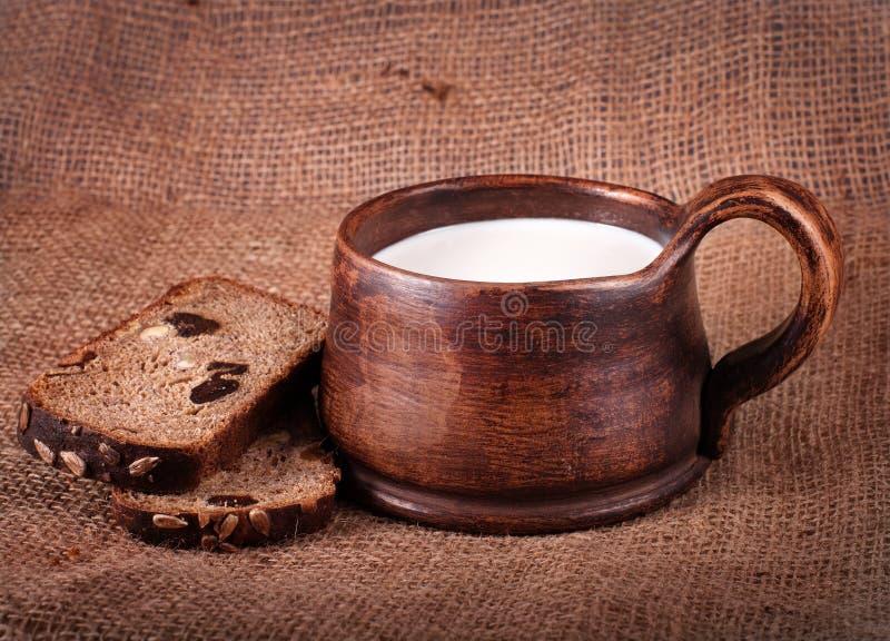 自创棕色黏土杯子用牛奶和面包 免版税库存图片