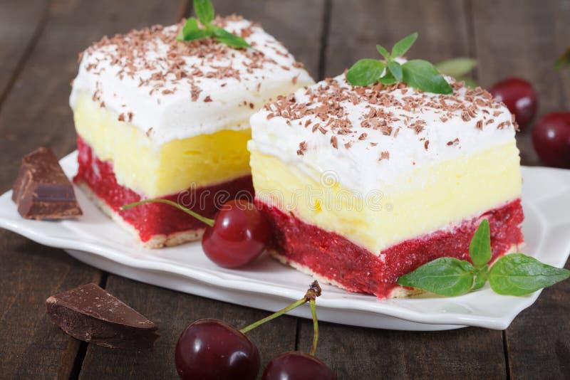自创樱桃蛋糕用香草和纯奶油在木桌上 免版税库存照片