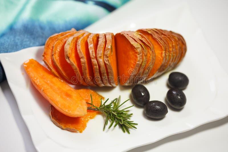 自创橙色白薯用橄榄和迷迭香 库存图片