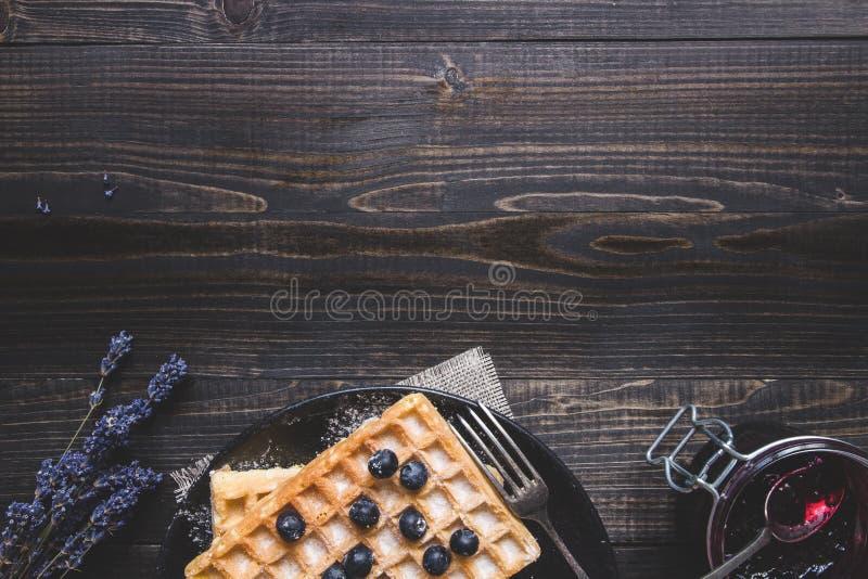 自创比利时华夫饼干用在黑暗的木桌上的蓝莓与拷贝空间 免版税库存照片