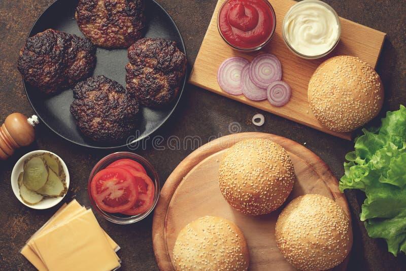 自创汉堡包的新鲜的成份在生锈的桌上 图库摄影
