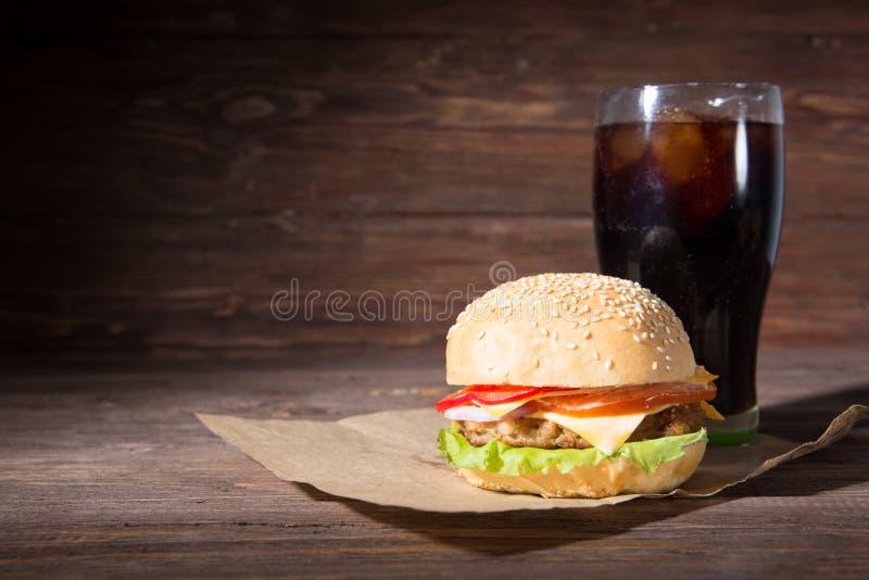 自创汉堡和冷的饮料可乐在木背景 免版税库存图片