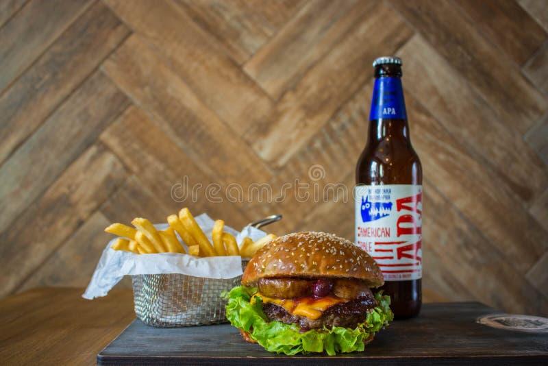 自创汉堡用牛肉梨和樱桃和法国油煎的土豆和瓶在木桌上的冰镇啤酒在木背景 免版税库存图片