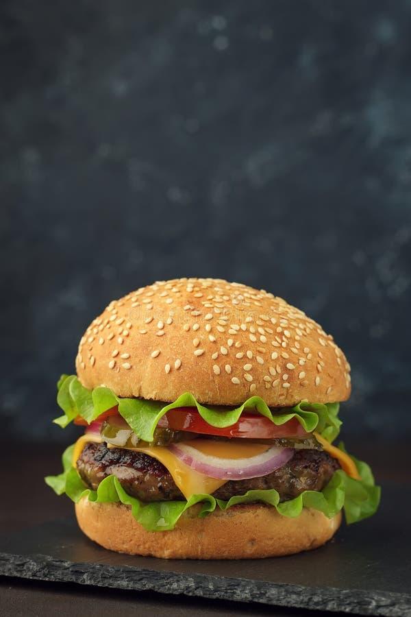 自创汉堡用牛肉,乳酪,蕃茄,葱,在石委员会的沙拉 免版税库存图片