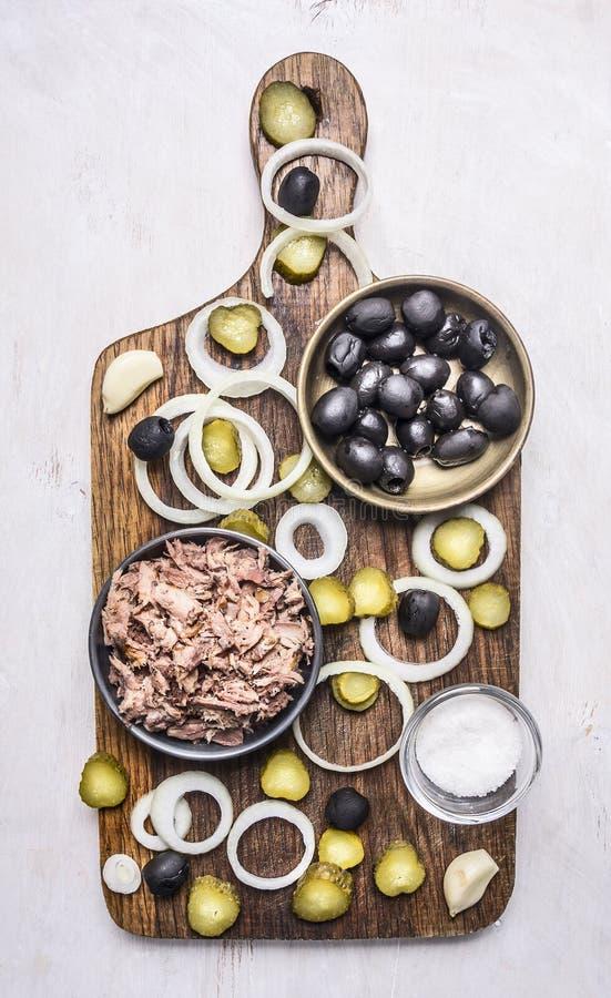 自创汉堡的,金枪鱼,小圆面包,调味汁,橄榄,香料成份,计划在切板木土气背景上面竞争 免版税库存图片