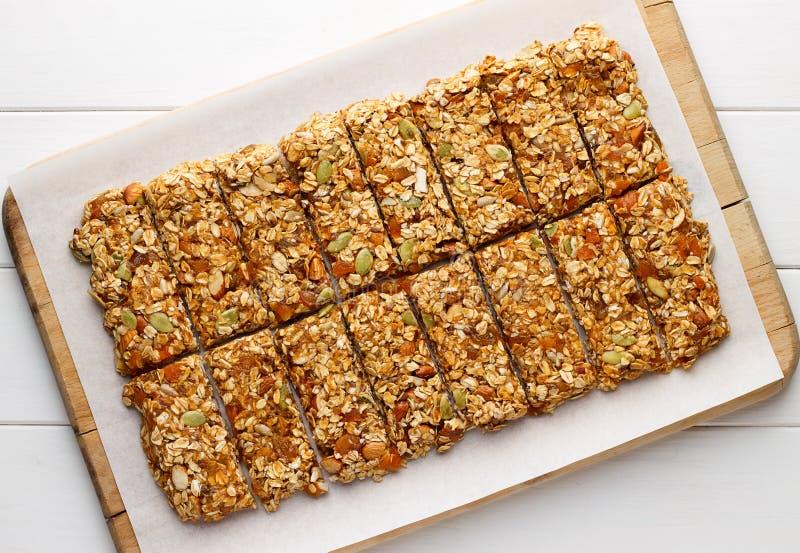 自创没有烘烤与燕麦剥落、蜂蜜、杏干和种子的格兰诺拉麦片棒在白色烘烤纸 免版税图库摄影