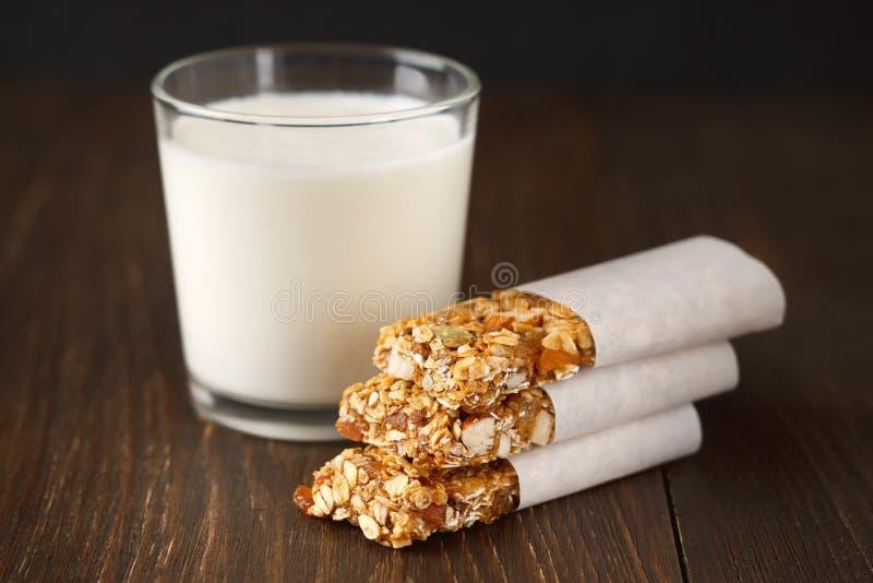 自创没有烘烤格兰诺拉麦片棒用燕麦、日期、蜂蜜和杏仁在木背景 免版税库存图片