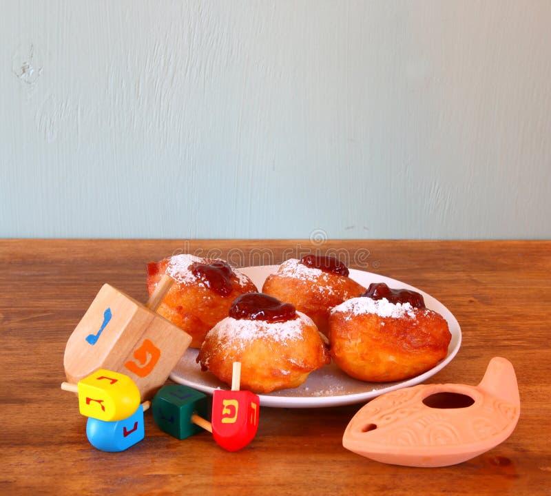 自创油炸圈饼和木dreidels (抽陀螺)为在木桌的光明节犹太假日 库存图片