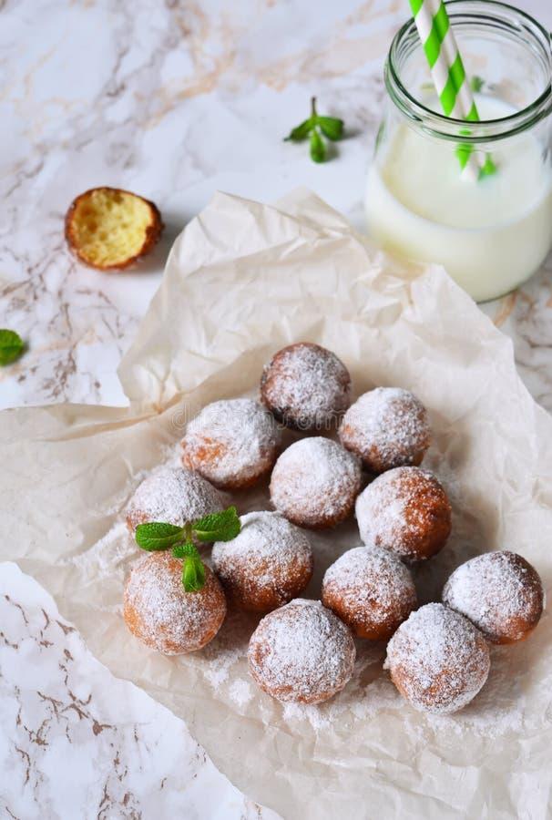 自创油炸圈饼用搽粉的糖和牛奶 免版税图库摄影