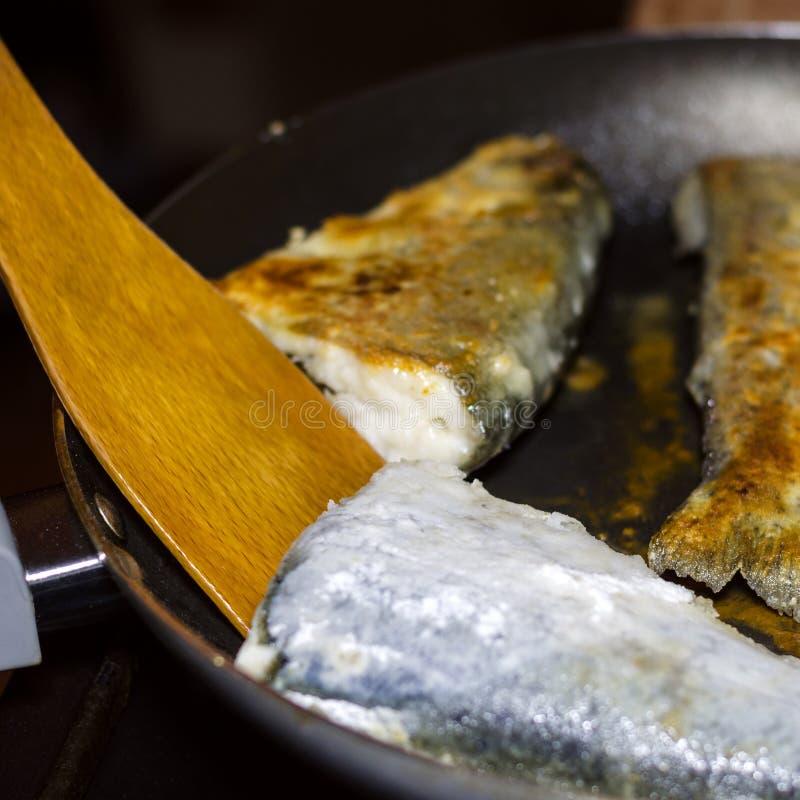 自创油煎的鱼无须鳕的准备在煎锅的 骗局 免版税库存照片