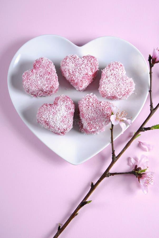 自创澳大利亚在心脏形状白色板材-垂直的样式桃红色心脏形状小lamington蛋糕 免版税库存照片