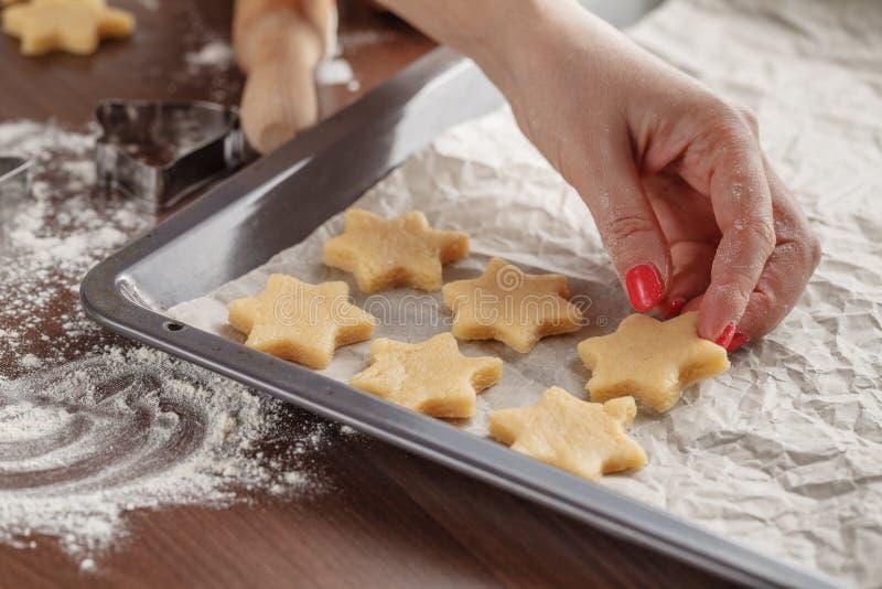 自创烘烤,显示妇女的厨房场面举行烘烤tra 库存照片