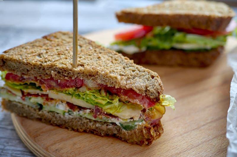 自创烟肉三明治有木背景 库存图片